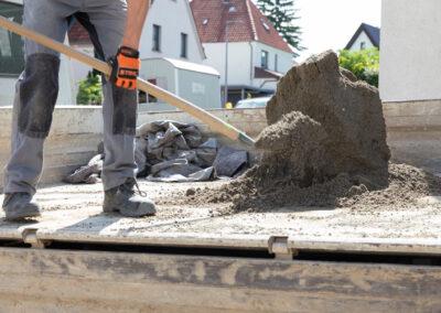 Gartenbau Siebert auf einer Baustelle Erde schippen